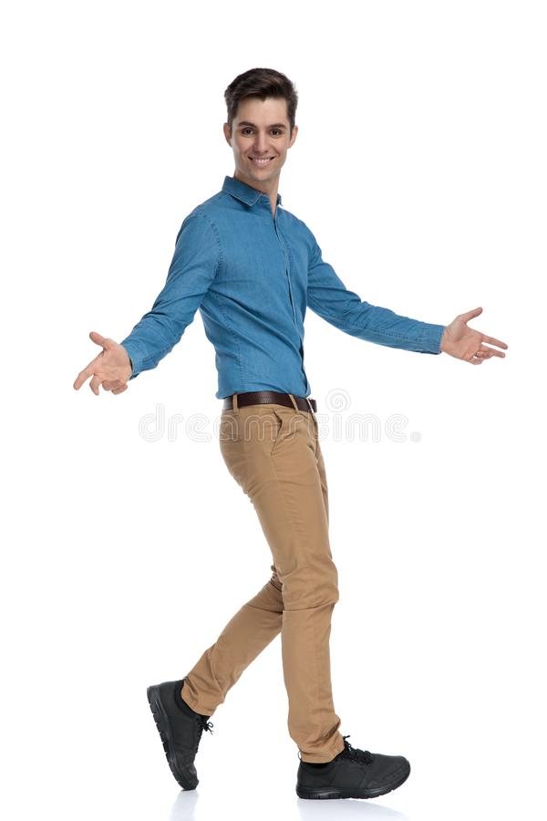 Side view of happy young man walking and opening arms. Side view of happy young man smiling and opening arms, presenting, walking  on white background, full body stock images