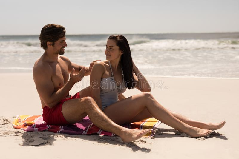 Man applying sunscreen lotion on woman back at beach royalty free stock photos