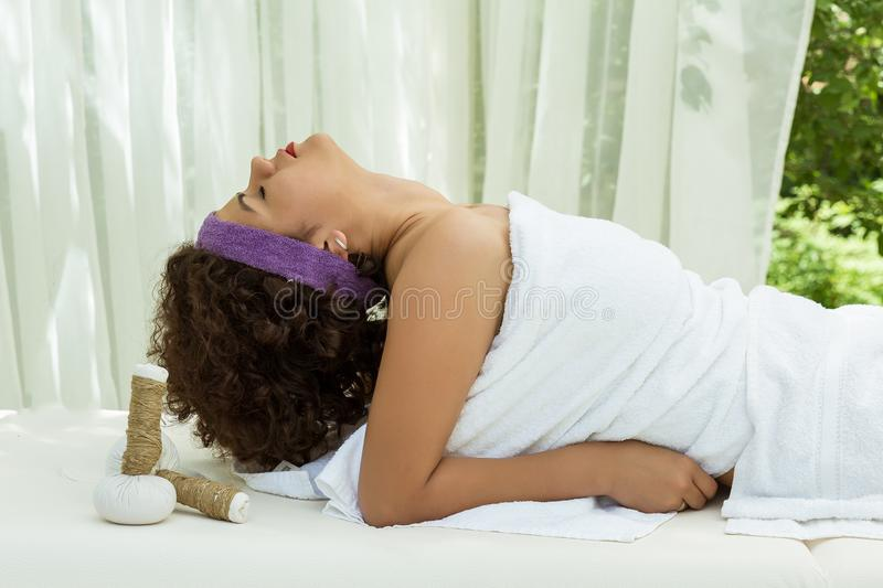Side view of happy young woman enjoying sitting on sofa relaxing with eyes closed stock image
