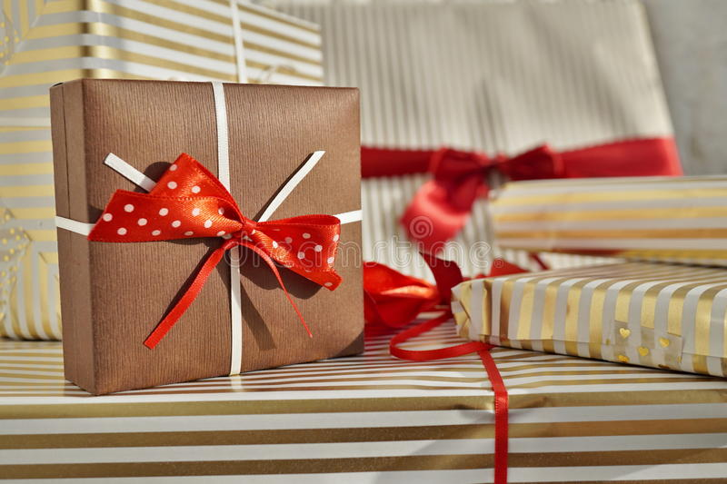 Side view of heap of gifts presents wrapped in lined wrapping paper royalty free stock photo