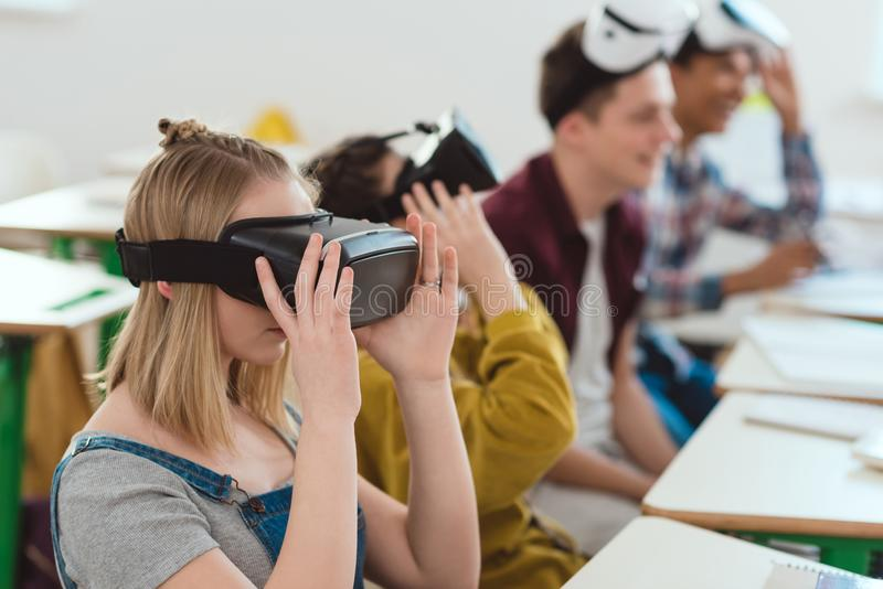 Side view of high school students taking off virtual reality. Headsets royalty free stock photos