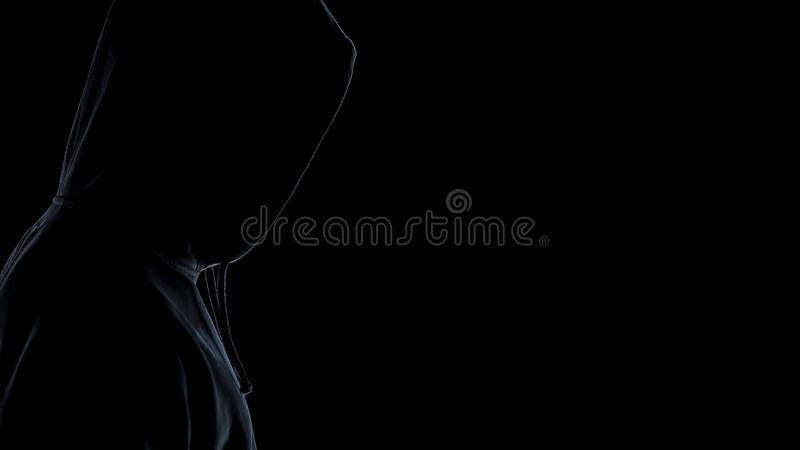 Side view of hooligan silhouette standing against dark background, close up royalty free stock photos