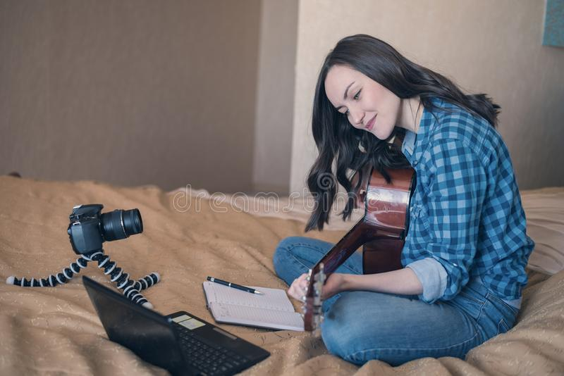 Side view horizontal image of a girl in casual clothes on the bed, records a music blog and plays acoustic guitar.  stock image