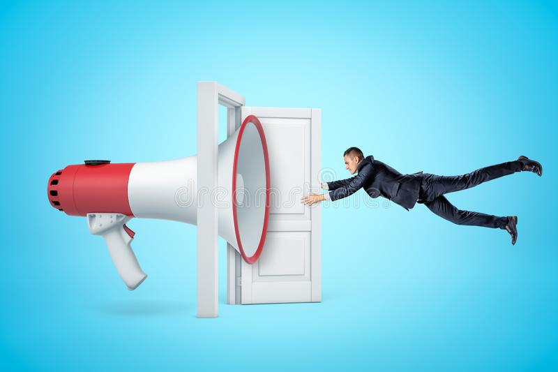 Side view of huge megaphone in open doorway knocking businessman off his feet with soundwave and making him grab at door stock photos