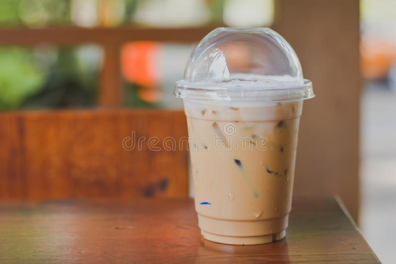 Side view Ice coffee cappuccino, latte, mocha in plastic cup with water drop on wooden column with blurry garden background with royalty free stock photos