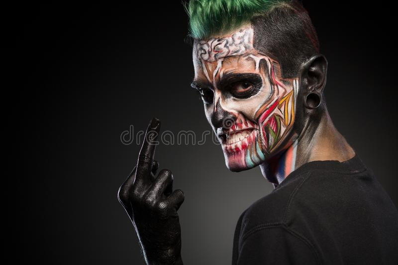 Side view if a man with colored skull makeup showing long finger. royalty free stock images