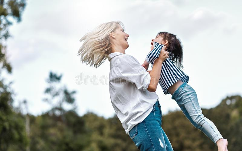 Side view image of happy little daughter playing with her smiling mother in the park. Loving woman and her little kid girl stock image