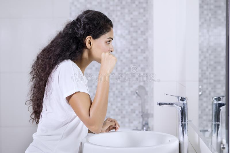 Indian woman brushes teeth in the bathroom stock image