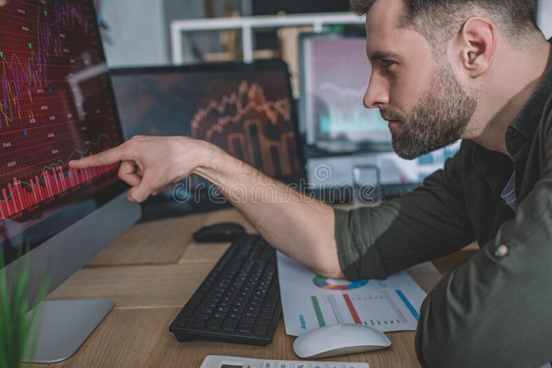 Side view of information security analyst pointing with finger on charts on computer monitor while working. In office royalty free stock images