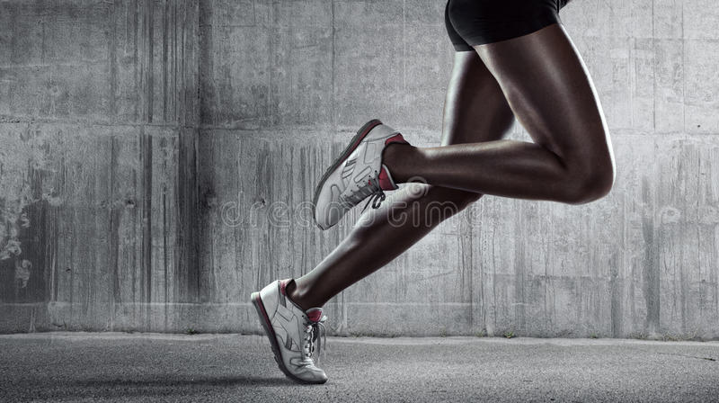 Side view of a jogger legs on concrete wall stock photography