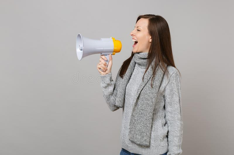 Side view of joyful young woman in gray sweater, scarf scream in megaphone isolated on grey wall background. Healthy royalty free stock photo
