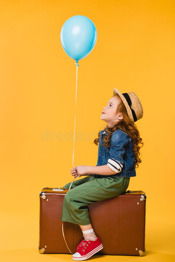 side view of kid with balloon sitting in suitcase stock photography