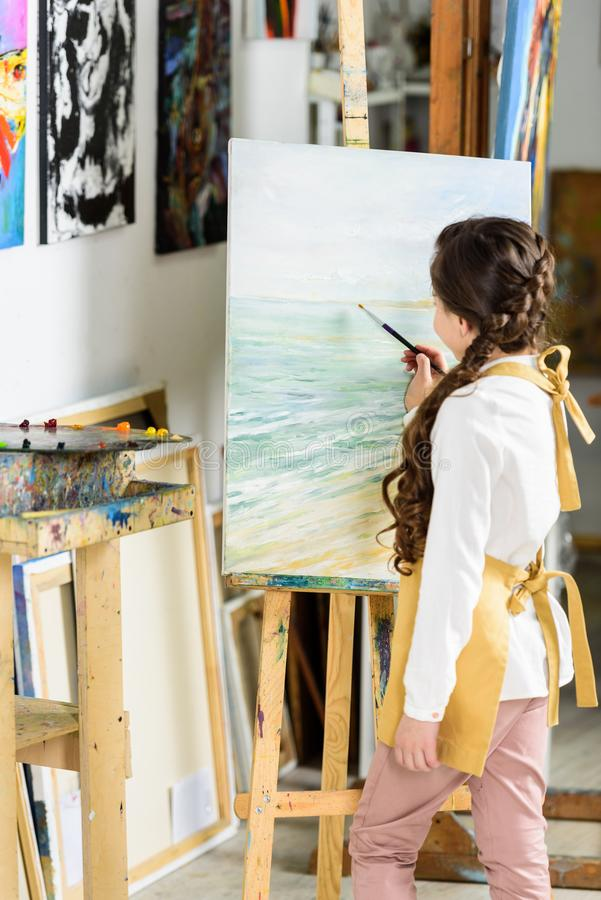 Side view of kid painting on canvas in workshop of. Art school stock images