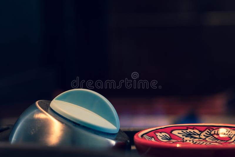 Egg timer on a kitchen surface, next to Asian theme large spoon - black background with copy space. stock photography