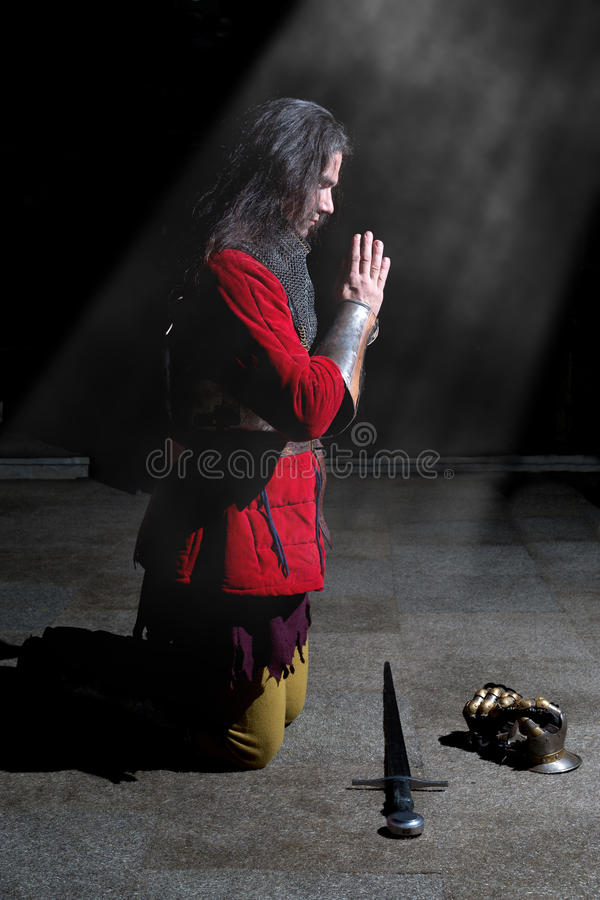 Side View of Knight Kneeling on His Knees and Praying. On Light Rays stock photos