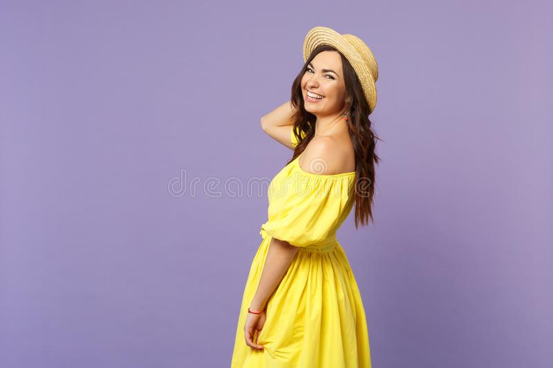 Side view of laughing happy young woman in yellow dress, summer hat looking camera  on pastel violet wall stock images