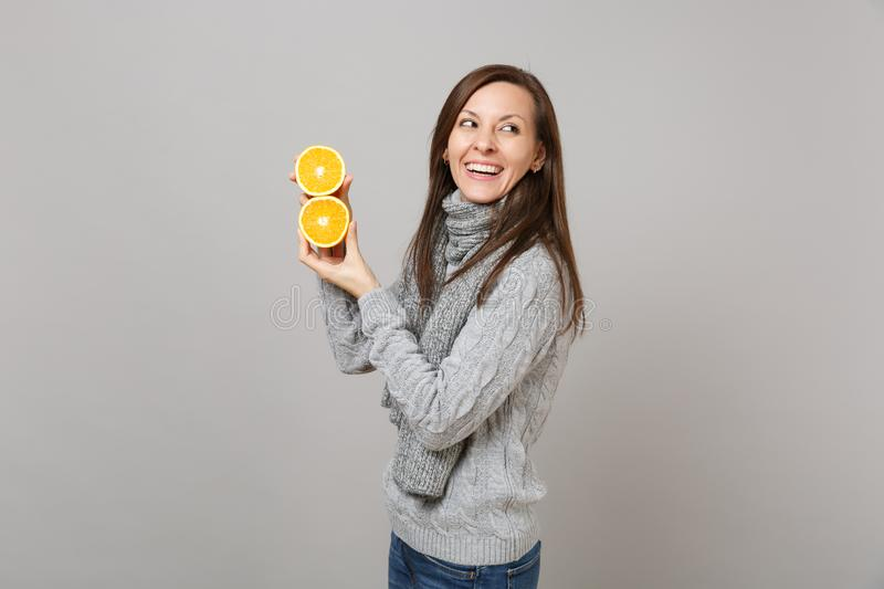 Side view of laughing young woman in gray sweater, scarf holding oranges isolated on grey wall background. Healthy royalty free stock photography