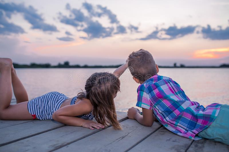 Side view of a little boy and a girl while lying on the wooden pier and and pointing away on the sky. Friendship, happy couple, first love stock photo