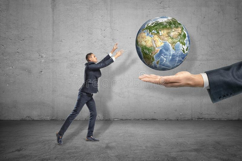 Side view of little businessman reaching out for planet Earth that is levitated above big man`s hand emerging from right. Collaboration. Global industry royalty free stock photography