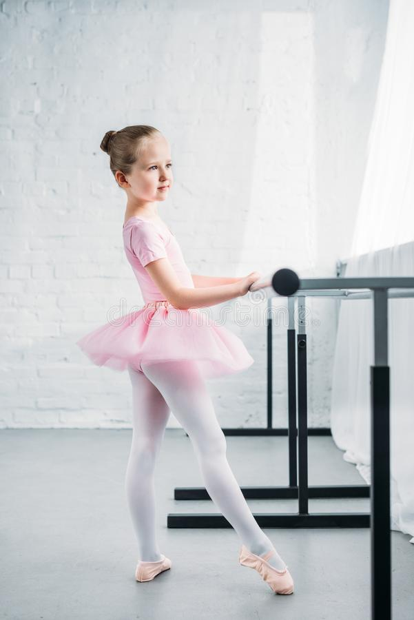 Side view of little child in pink tutu practicing ballet in ballet school stock photography