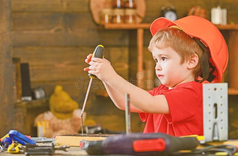 Side view little kid binding into wooden block. Concentrated boy in orange helmet sitting at table and holding royalty free stock photography