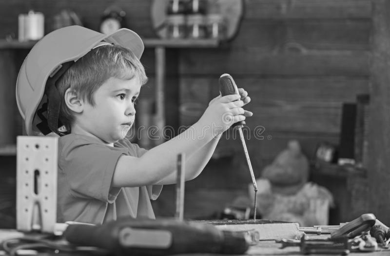 Side view little kid binding screw into wooden block. Concentrated boy in orange helmet sitting at table and holding stock images