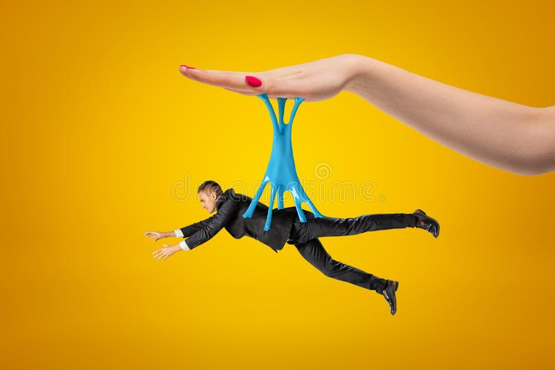 Side view of little man in suit hanging on blue sticky slime stuck to big woman`s hand above on yellow background. E view of little man in suit hanging on blue stock image