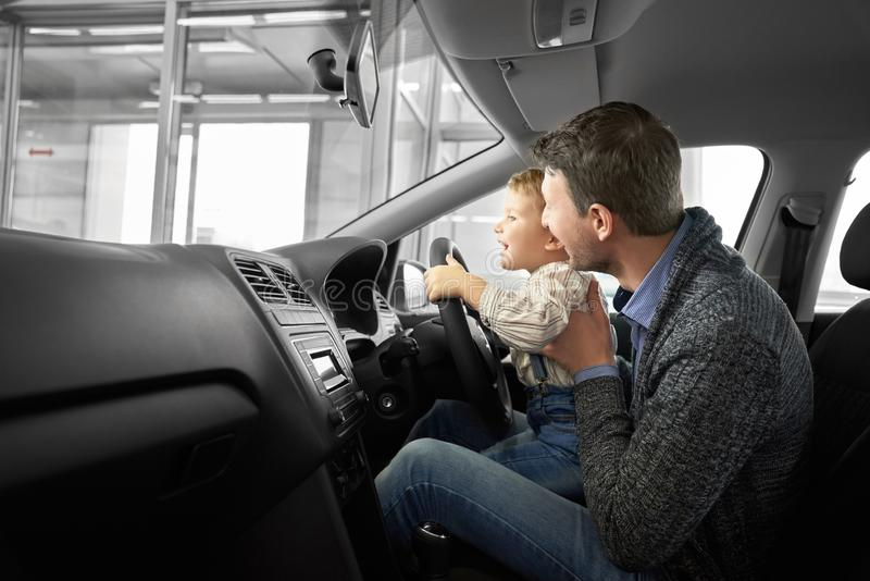 Lovely family testing comfortable machine in auto salon royalty free stock photo