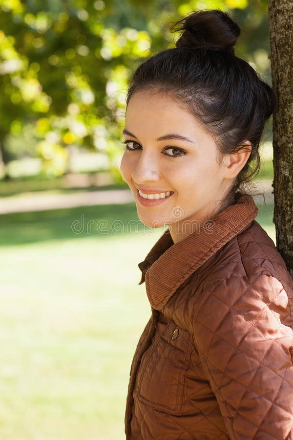 Side view of lovely woman leaning against a tree stock photos