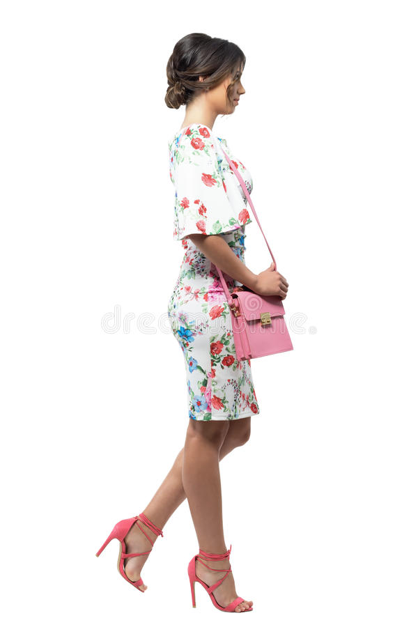 Side view of luxurious elegant fashion woman with pink bag walking and looking away. royalty free stock image