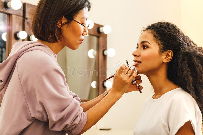 Side view of a makeup artist applying lip paint. With a brush royalty free stock image