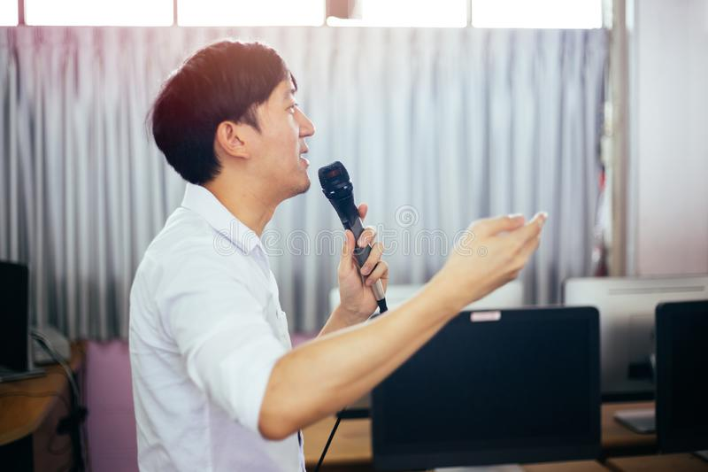 Side view of businessman speaking and making a lecture in public speaking event in the room. Side view of male Asian businessman speaking and making a lecture in stock images
