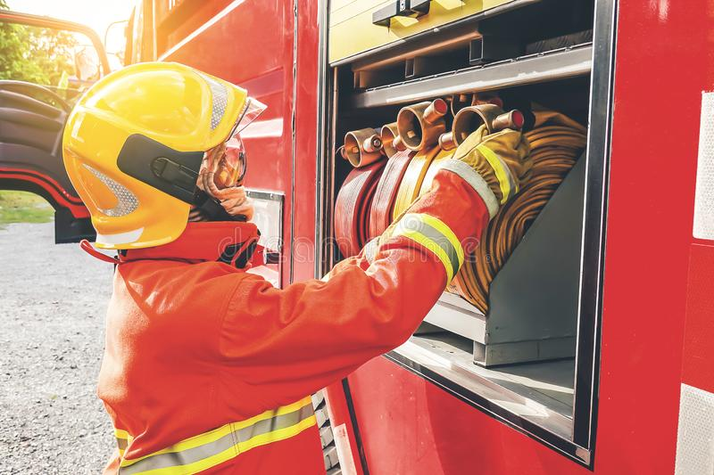 Side view of male firefighter fixing water hose in truck royalty free stock photography