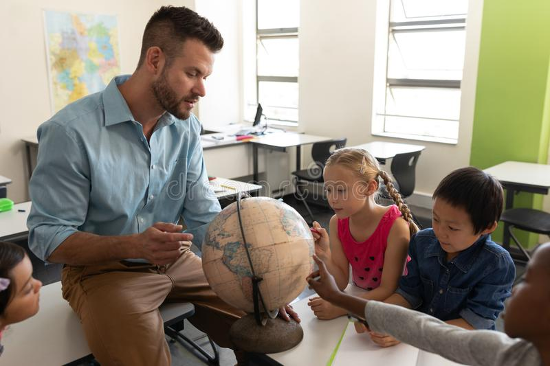 Side view of male teacher teaching his kids about geography by using globe in classroom stock photo
