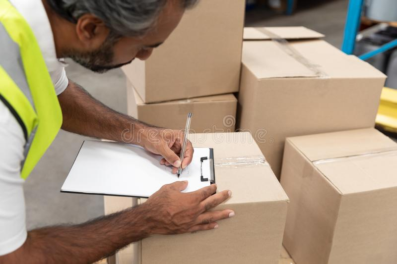 Male worker writing on clipboard in warehouse. Side view of male worker writing on clipboard in warehouse. This is a freight transportation and distribution stock photography