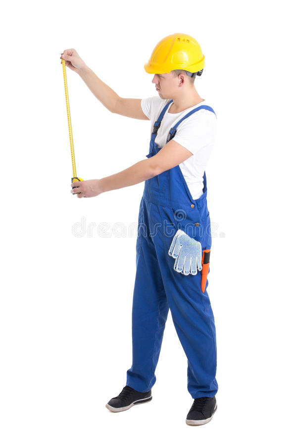 Side view of man builder in blue coveralls holding measure tape. Isolated on white background stock photography