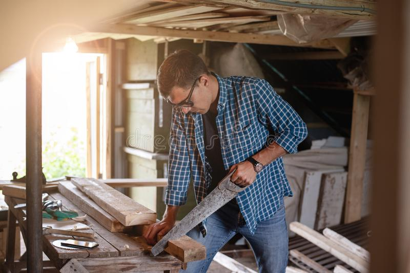 Side view of a man carpenter with glasses sawing a wooden Board in the home workshop royalty free stock photos