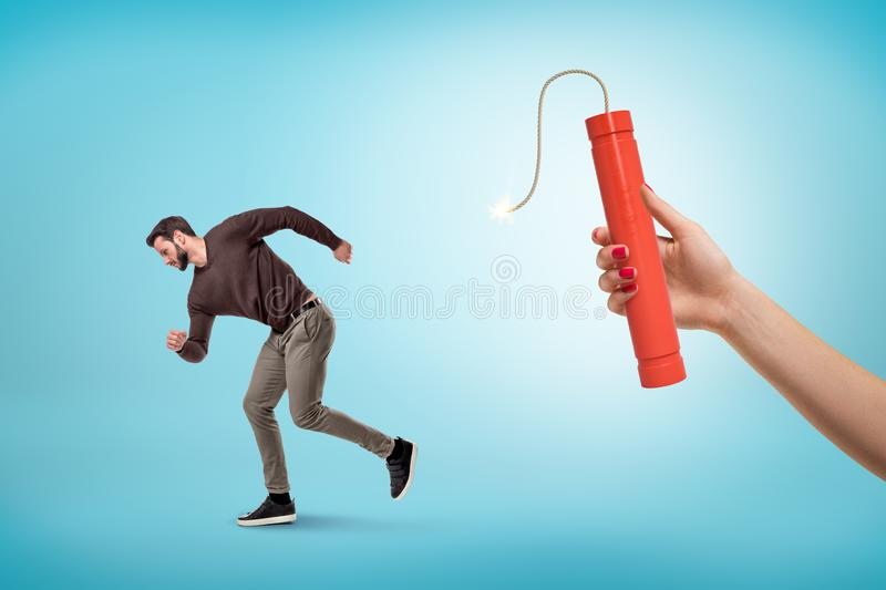 Side view of man in casual outfit running away from female`s hand holding lit dynamite stick. stock image