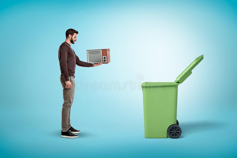 Side view of a man in a casual outfit standing near an open trash can and holding a little old-fashioned TV set. Recycle and reuse. Get rid of old trash. Say royalty free stock photography