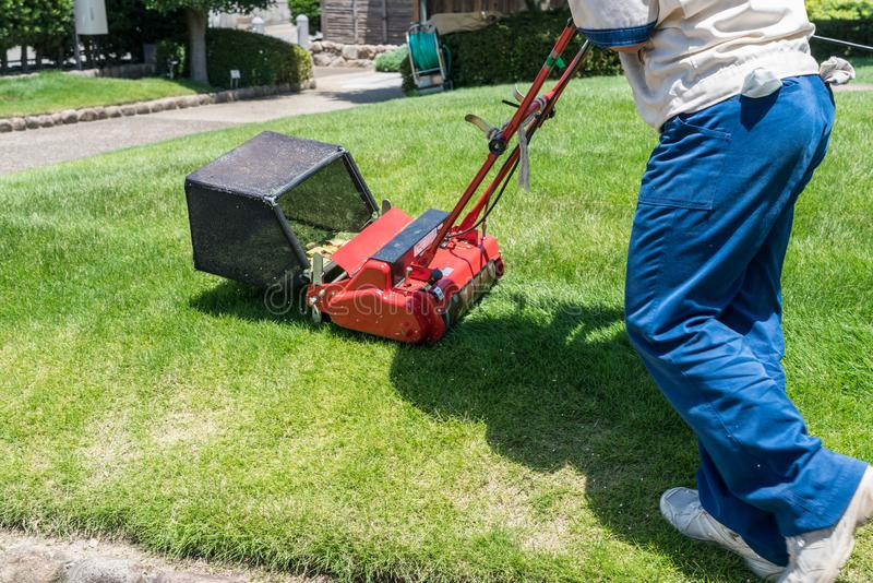 Side view of man cutting grass with lawn mover stock photos