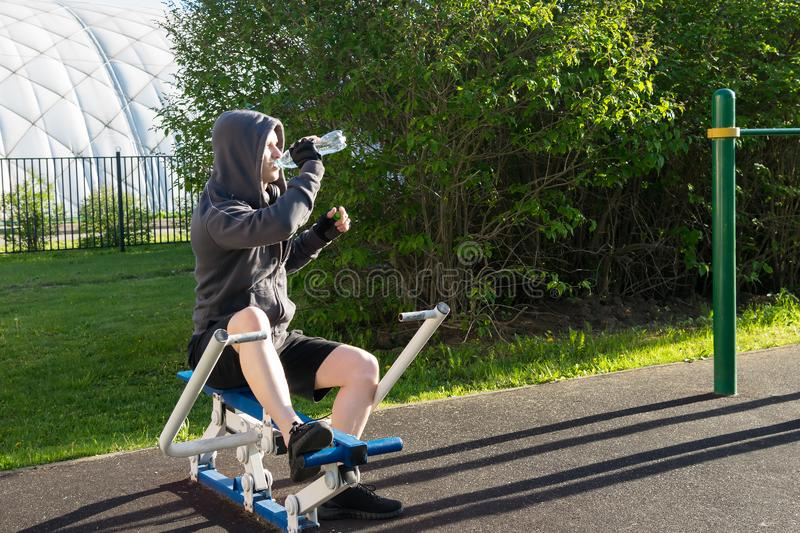 Side view of a man doing abs exercises using a simulator on a sports ground on a street stock photography