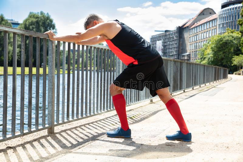 Man Doing Push-Ups On Railing. Side View Of A Man Doing Push-Ups On Railing At Outdoors royalty free stock photography