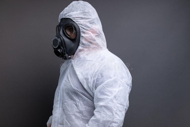 Side view of man with gas mask in protective overall suit against grey background royalty free stock photos