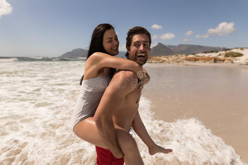 Man giving woman piggyback ride and having fun at beach royalty free stock photography