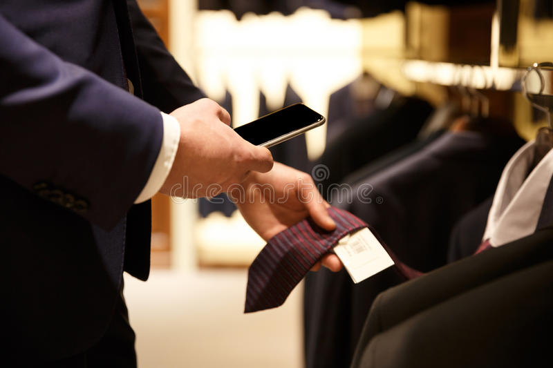 Side view of man making photo of price-list. Side view of man in suit making photo of price-list on his smartphone while being in shop. Cropped image stock image