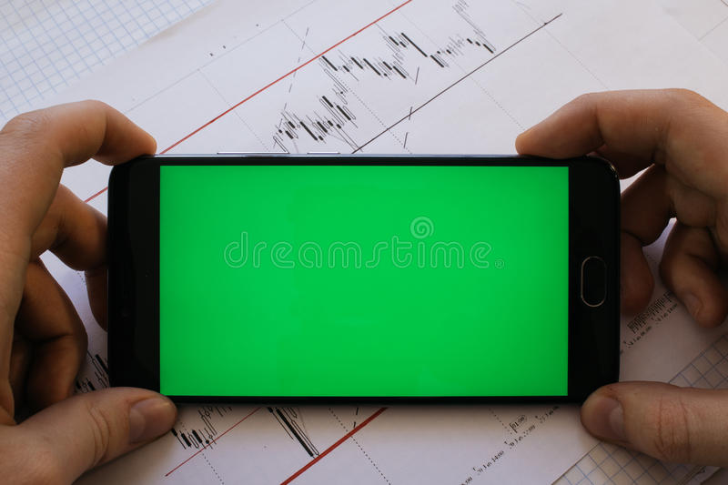 Side view of a man with a marker and stable standing against a c. Oncrete wall with graphs drawn on it. Concept of statistics and stocks With the green screen royalty free stock image