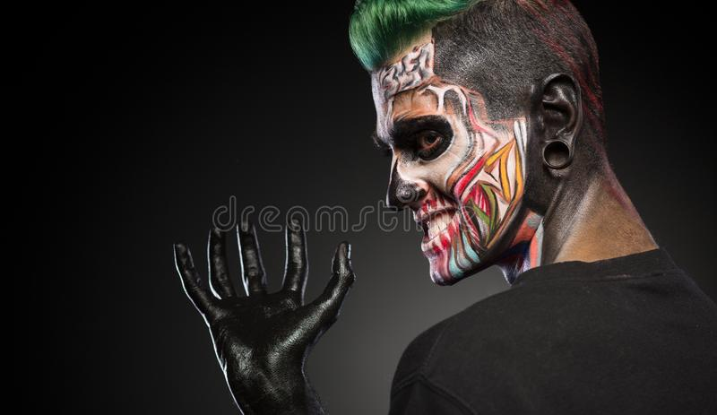 Side view of a man with monster face make up and hand painted in black. Mystical face art, man with skull makeup royalty free stock photos