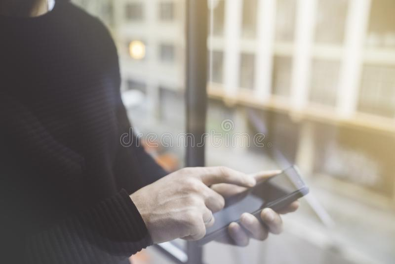 Side view of a man`s hands pointing finger smart phone in interior.Rear view of business man hands busy using cell phone. At office.Young male coworker typing royalty free stock photos