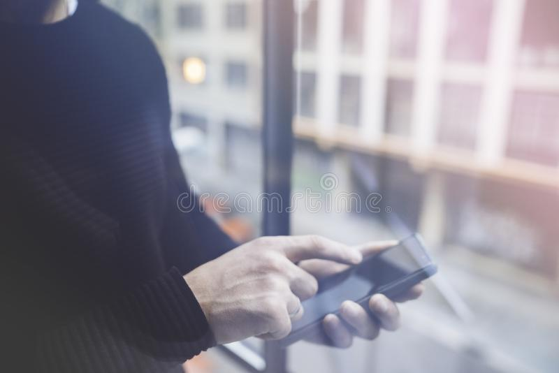 Side view of a man`s hands pointing finger smart phone in interior.Rear view of business man hands busy using cell phone. At office.Young male coworker typing stock photography