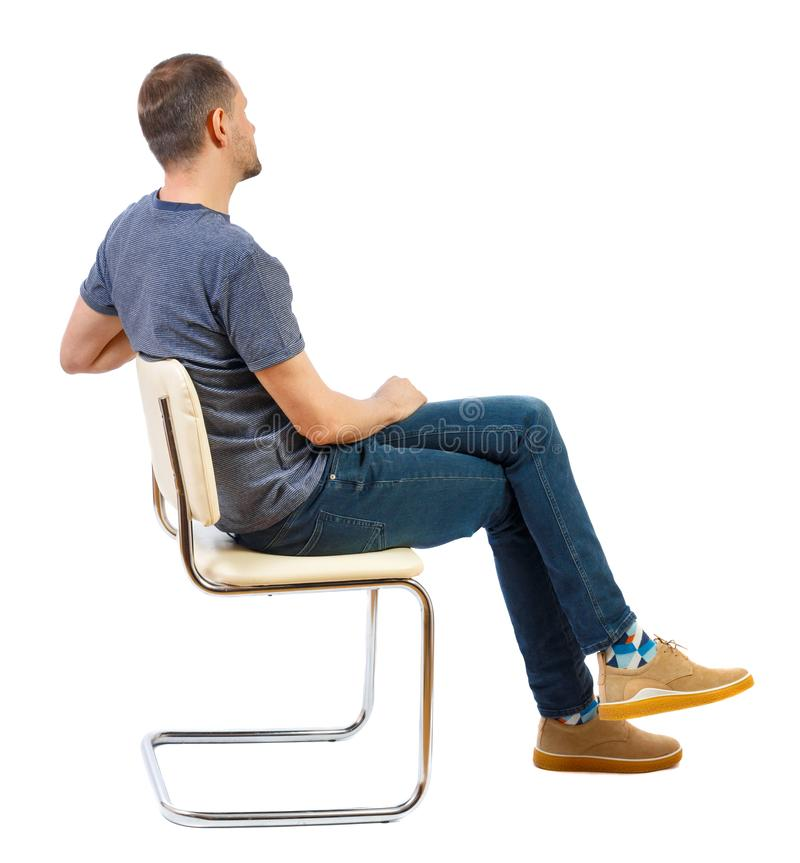 Side view of a man sitting on a chair stock images